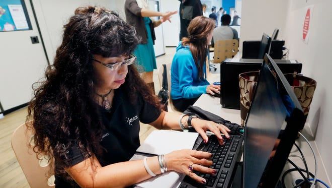 Dorathy Vargas, foreground, uses a computer to search for a job at the office of CONNECT, a coalition of local organizations that provides employment services in Chelsea, Mass.