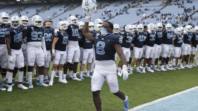 Running back Michael Carter leads North Carolina's celebration after a victory against Virginia Tech two weeks ago in Chapel Hill.