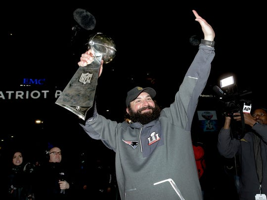 Patriots defensive coordinator Matt Patricia raises