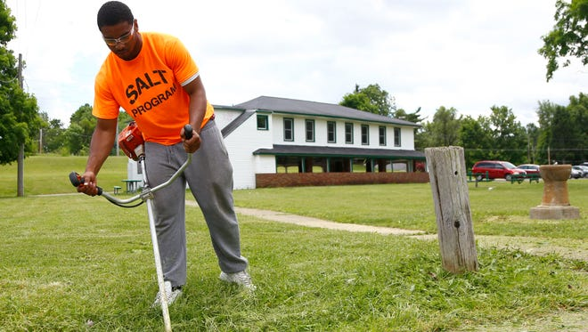 Caleb Macklin cuts down weeds at Liberty Park on Tuesday. Macklin is part of the Student Achievement Leadership Training summer program, which gives career planning, work experience and personal finance training to area students.