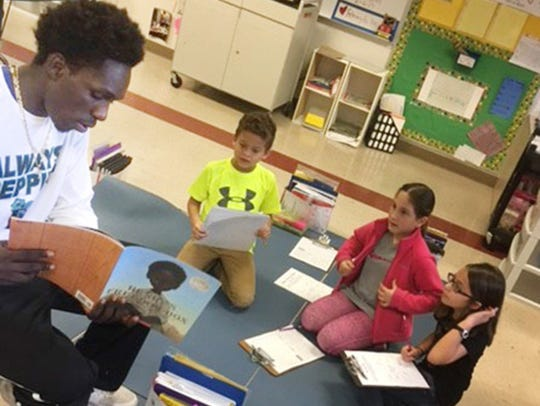 Todd Exume (left) of Bayside High basketball read to third-grade students at Westside Elementary last week.
