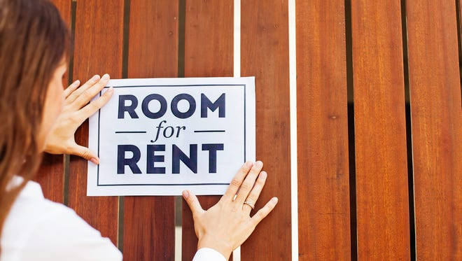 """Woman attaching a """"room for rent"""" sign to a wall"""
