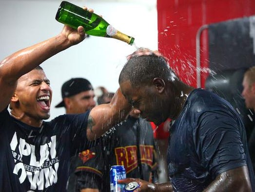 The Red Wings' Eduardo Escobar baths Deibinson Romero, right, with champagne while celebrating the team's wild card berth on the final day of the regular season at Frontier Field.