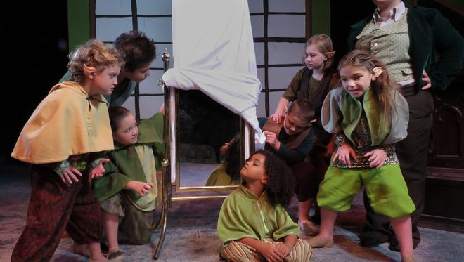 Young hobgoblins peak under the sheets of a new invention by their professor in one of the scenes from the Pensacola Little Theatre production of the Snow Queen.