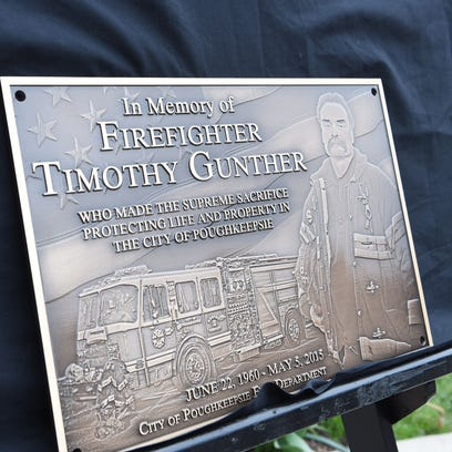 City of Poughkeepsie firefighters Lt. Steve Bauer, left, and Paul Bucher, right, unveil the memorial plaque dedicated to Tim Gunther, who died in May 2015 while responding to a fire.