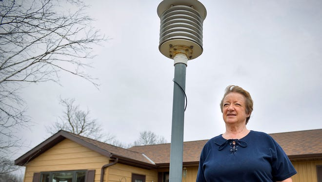 "Bonnie Zutz inspects a ""beehive"" digital thermometer April 1 at her rural Kimball home. The thermometer registers daily temperatures on a device inside her house. Zutz is one of more than 200 official weather reporters in Minnesota."