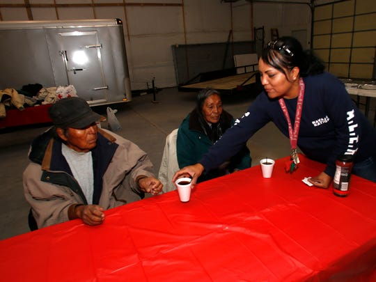 Volunteer Beronica Barber serves coffee to Cecil Billie and Marlene Cloud during an event to feed the homeless at the Shiprock Events Center.