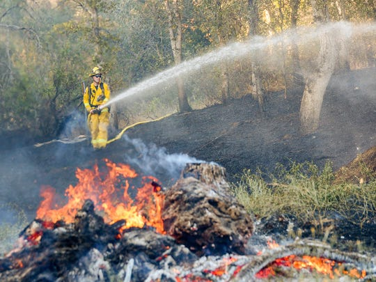 A firefighter sprays water Tuesday evening on a 3-acre