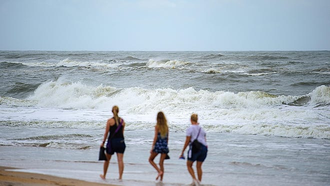 Three women walk along Vilano Beach on Monday as Tropical Storm Isaias passes the area offshore.