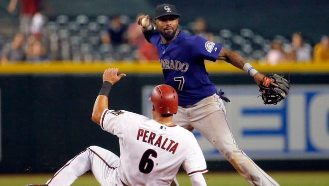 FILE - In this Sept. 29, 2015, file photo, Arizona Diamondbacks left fielder David Peralta (6) is forced out at second as Colorado Rockies shortstop Jose Reyes (7) turns a double play in the sixth inning of a baseball game in Phoenix. The New York Mets have signed Reyes to a minor league contract, Saturday.  Reyes, 33, played primarily at shortstop for the Mets from 2003-11, but may be used in a utility role in his reunion with the team. He was cut by Colorado after serving a 59-day suspension for violating Major League Baseball's domestic violence policy. (AP Photo/Matt York, File)
