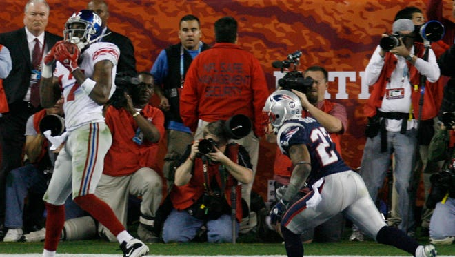 New York Giants receiver Plaxico Burress, left, scores a touchdown in the fourth quarter during the Super Bowl XLII football game against the New England Patriots at University of Phoenix Stadium on Sunday, Feb. 3, 2008 in Glendale, Ariz.