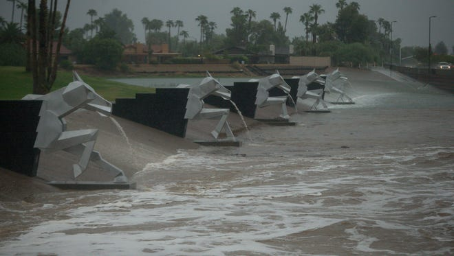 The horse sculptures begin to spout water as the Indian Bend Wash overflows in Scottsdale, as more than 3 inches of rain falls in the early morning, Monday, Sept. 8, 2014. The remnants of Hurricane Norbert caused flooding throughout the Phoenix area.