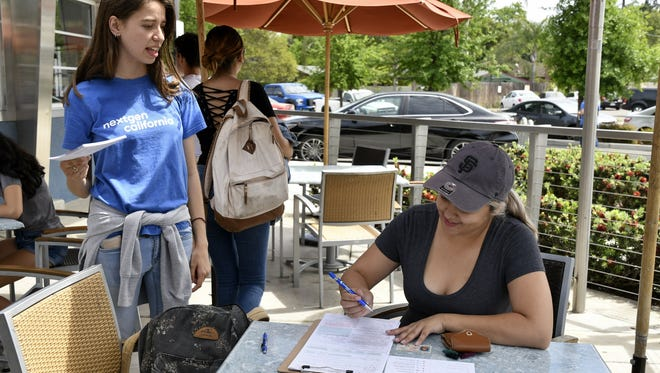 NextGen California Fellowship member Katelyn Nee helps COS student Ashton Noland, 22, register to vote during an event on Tuesday at The Habit Burger Grill in Visalia.