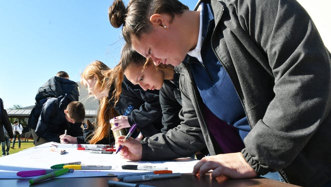 Wednesday morning, March 14. Students, teachers, and staff at Holy Trinity Episcopal Academy in Melbourne honored the victims of the Parkland shooting with a candle lighting ceremony, a reading of the names, a gathering around the flag, signing a banner to send to Marjory Stoneman Douglas High in Parkland, and making wrist bands in memory of the victims of violence.