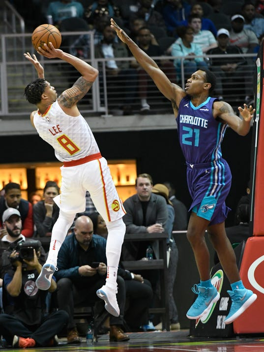 Atlanta Hawks forward Damion Lee, left, puts up a shot as Charlotte Hornets guard Treveon Graham, right, defends during the second half of an NBA basketball game Thursday, March 15, 2018, in Atlanta. Charlotte won 129-117. (AP Photo/John Amis)