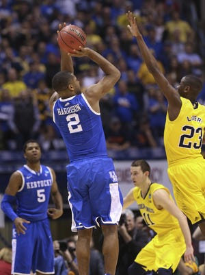 UK's Aaron Harrison, #2, shoots the game winning shot over Michigan's Caris LeVert, #23, during their Elite 8 game at the Lucas Oil Stadium in Indianapolis. Mar. 30, 2014