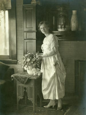 Elisabeth Ball is shown arranging flowers in her family home, Oakhurst, around 1915.