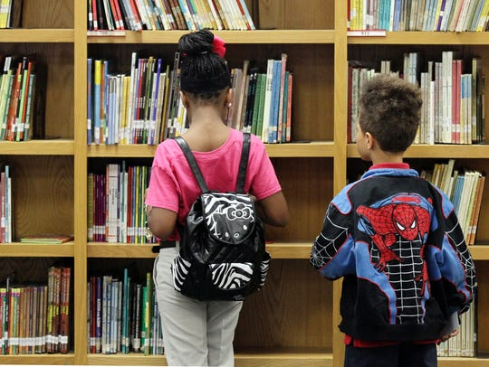 Students look through library books at J.W. Faulk Elementary