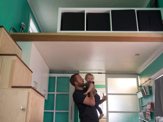 Jared Stoltzfus and his daughter, Dahlia Stoltzfus in the kitchen of his 160 square-foot tiny house in Scottsdale. The loft is above Jared.