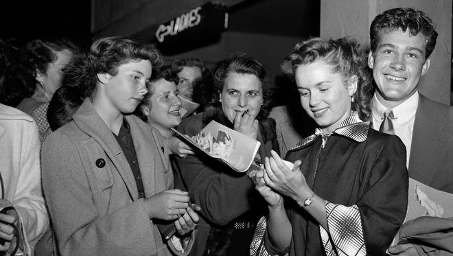 Actress Debbie Reynolds signs autographs on her way into an ice show in Hollywood on May 7, 1951. Her escort is Jack Larson.