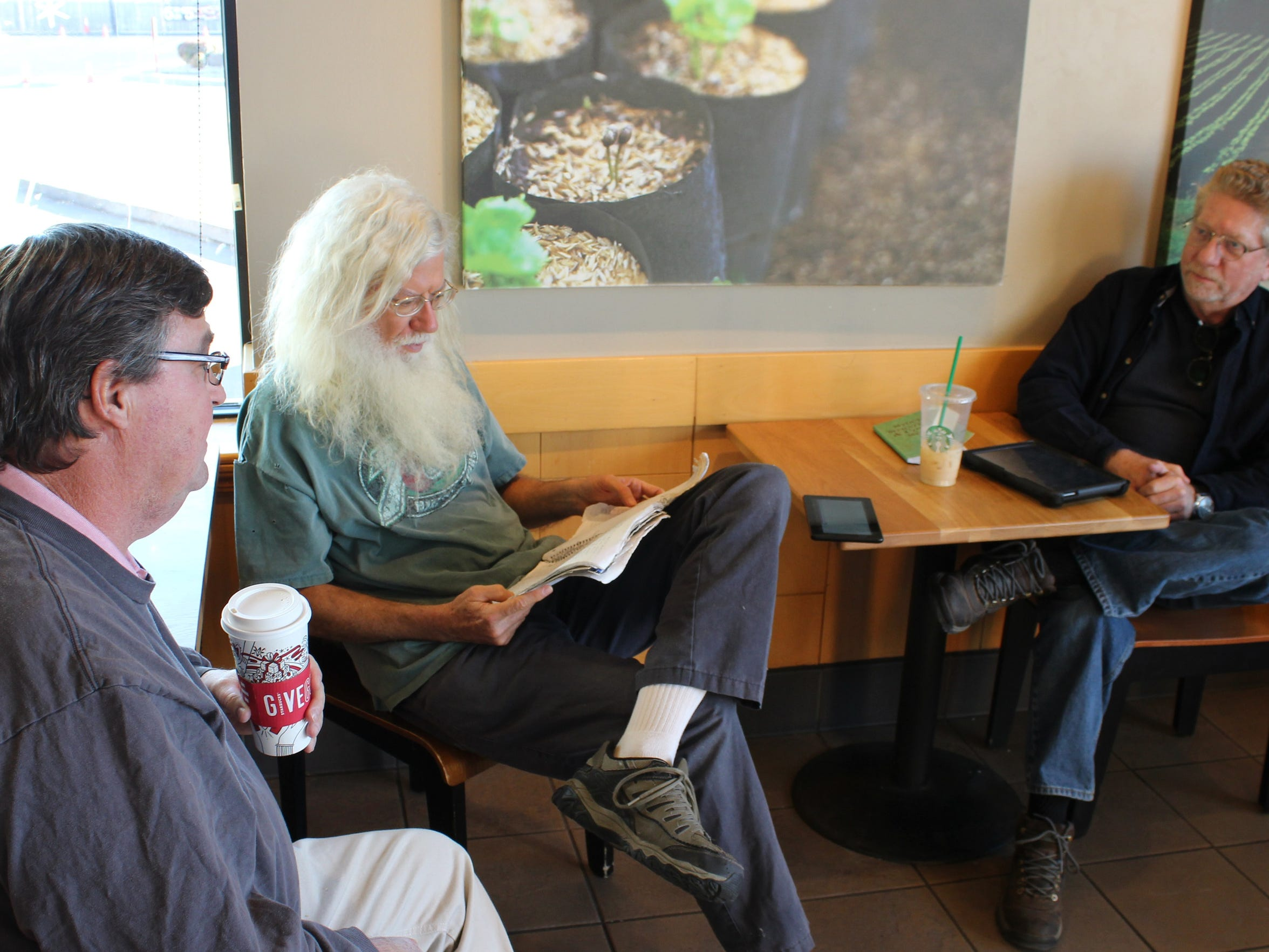 Rick Armstrong, left, and Gary Peterson, right, meet James Perkins at the Starbucks on South 14th Street to talk about what is going on in the stock market.