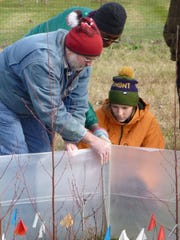 UVM LANDS Program students Shannon Scarbrough (right) and Flore Costumé help Carl Waite, a researcher from the Rubenstein School of Environment and Natural Resources, place plastic windbreaks around climate change research plots in mid-November. Waite is also a program coordinator for the Vermont Monitoring Cooperative.