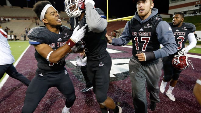 New Mexico State  linebacker Terrill Hanks, center, made a game clinching interception with his ankles on Saturday against Idaho.