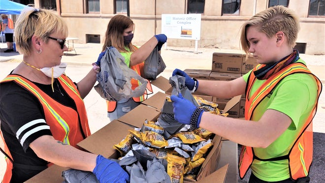 Renee Taylor, left, of NeighborWorks of Southern Colorado, and her daughters, Kennedy and Bridget, prepare food for giveaway during the June mobile pantry.