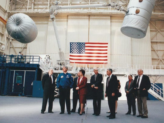 Carolyn Huntoon is shown in 1994 showing President Clinton and others the Space Vehicle Mock-up Facility inside Building 9 of the Johnson Space Center in Houston. Inside are several Space Shuttle mock-ups. The building is primarily used for astronaut training and systems familiarization.