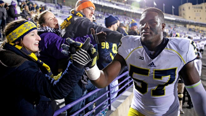 Michigan defensive end Frank Clark celebrates with fans after defeating Northwestern in Evanston, Ill., on Nov. 8, 2014.