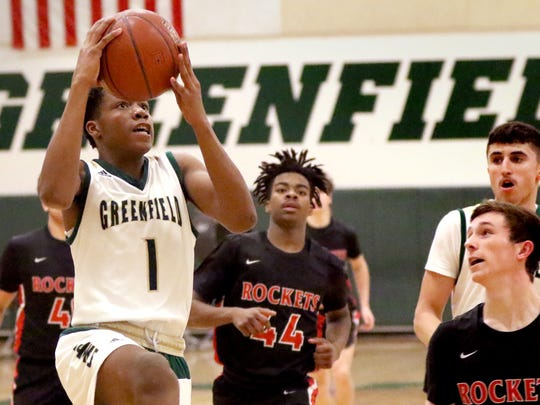 Greenfield's O'Marion Bartett heads for two points through South Milwaukee defenders at Greenfield on Feb. 2.