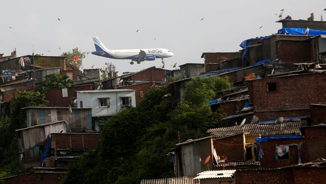 This file photo from June 15, 2016, shows an aircraft of private Indian airline Indigo flying above shanties adjacent to the Chhatrapati Shivaji airport in Mumbai, India.