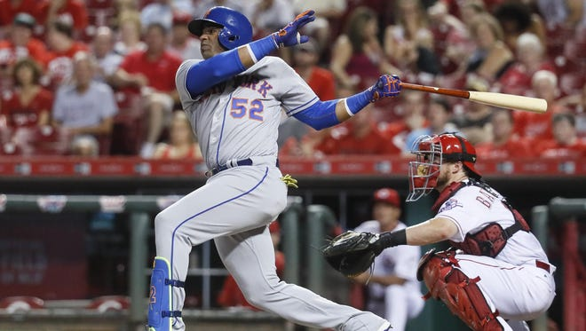 The Mets' Yoenis Cespedes follows through on a two-run home run off Cincinnati Reds relief pitcher Michael Lorenzen during the seventh inning of Tuesday night's game in Cincinnati. The Mets won 5-3.