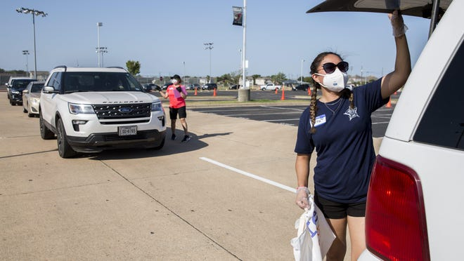 Volunteer Ruth Garcia loads a bag of personal protective equipment during a community PPE distribution event at Del Valle High School on Aug. 29. State health officials have updated the methodology for reporting the positivity rate of the coronavirus, or the percent of positive tests out of total tests. The update shows that the positivity rate was higher than previously thought as the state reopened in May and June.