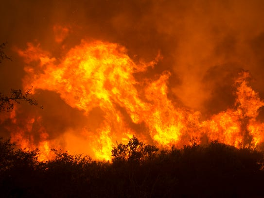 Flames from a wildfire burn Monday, Oct. 9, 2017, in
