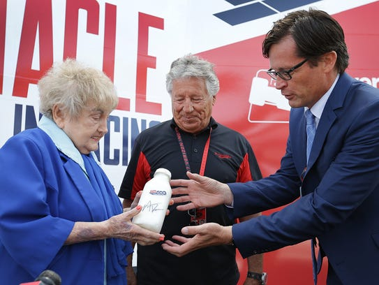 Eva Kor is presented with a bottle of milk from Mario