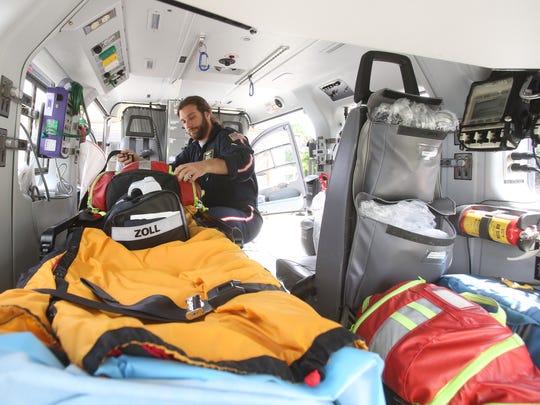 Flight nurse Michael Collura checks equipment on LifeNet