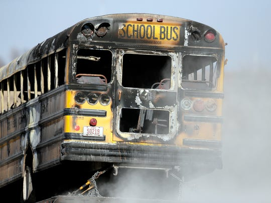 A burned school bus is transported by trailer near Oakland, Iowa, Tuesday, Dec. 12, 2017. A fire aboard the school bus has killed a student and the bus driver. Investigators say no one else was on the bus when it backed into a ditch and caught fire around 7 a.m. (AP Photo/Nati Harnik)