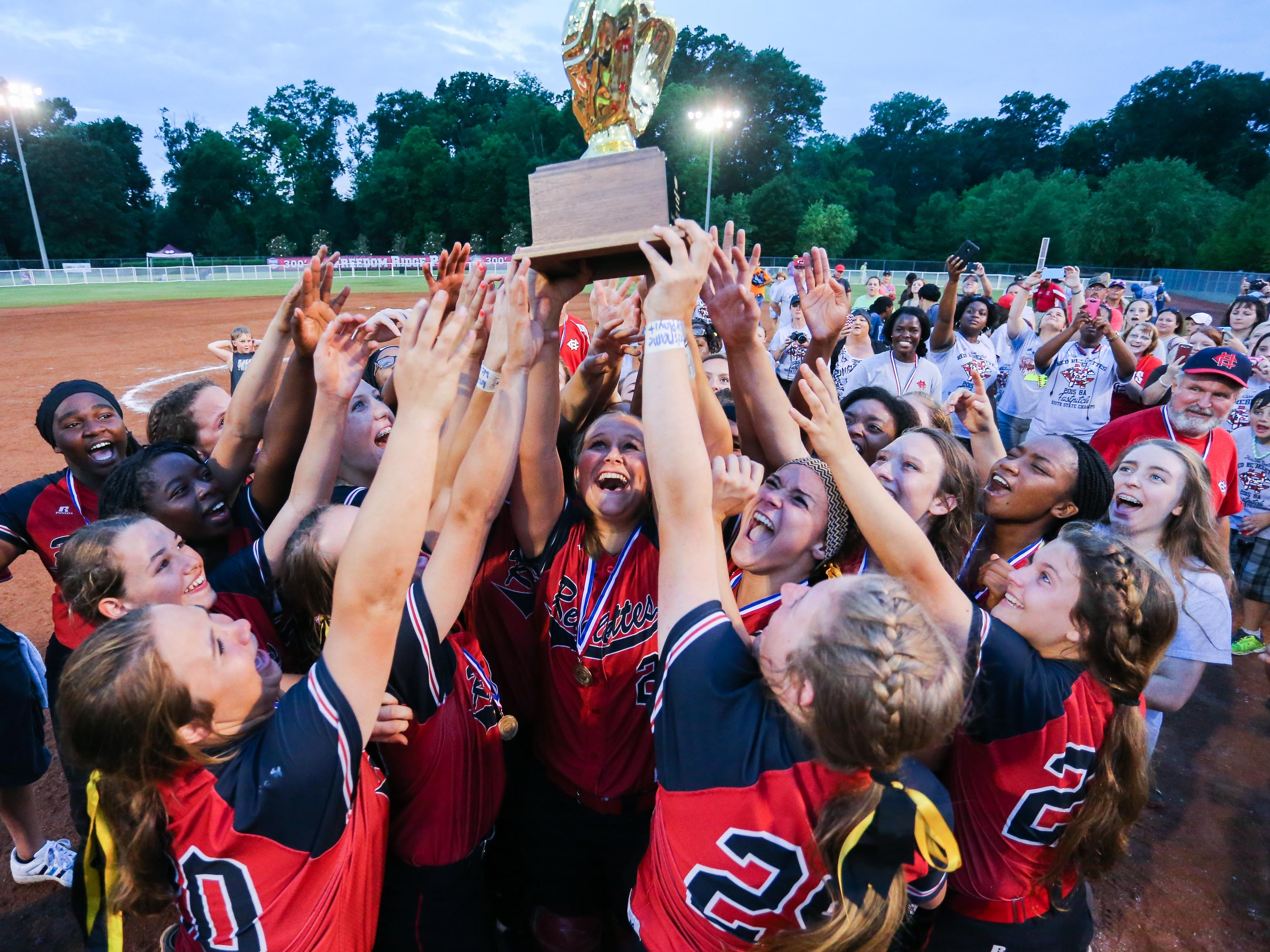 Harrison Central players hoist the trophy after their 9-1 win over Madison Central in the MHSAA Class 6A softball championship in Ridgeland on Saturday.