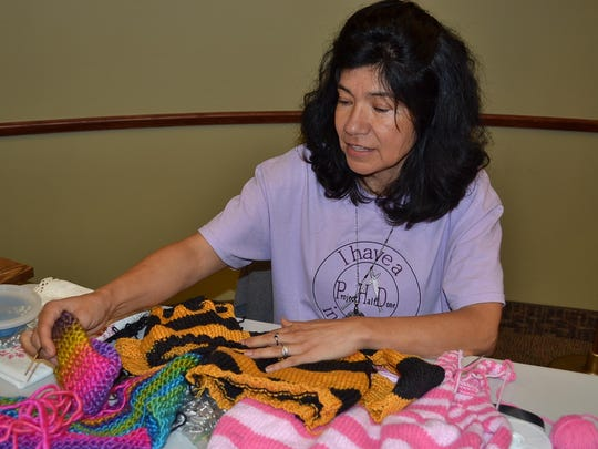 Nelcy Elder talks about the many projects she was working on at the Saturday Sew-In, including crocheting, embroidery and recycled projects. She also brought a stack of cloth squares made from jean material that she planned to piece together into a quilt.