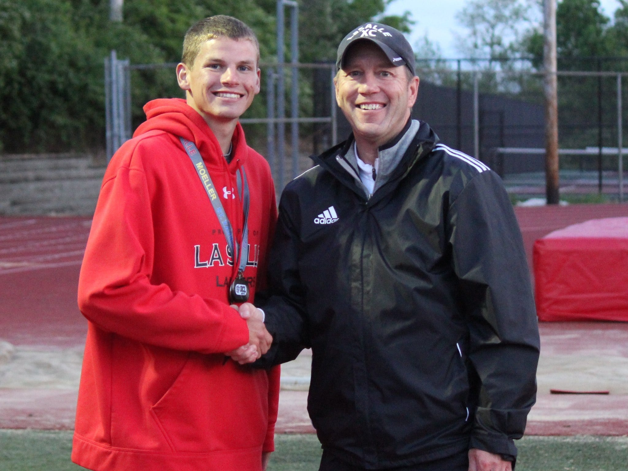 La Salle senior Tyler Harmon, a track standout for the Lancers, pictured with La Salle coach Frank Russo after a meet in the 2014 season.
