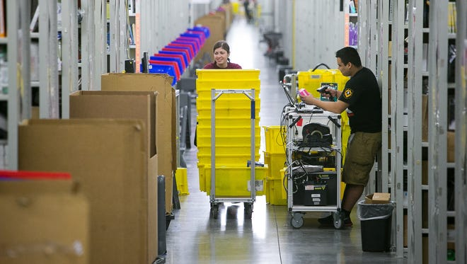 Amanda Bailey pushes a cart for items at the Amazon Fulfillment Center in Phoenix.