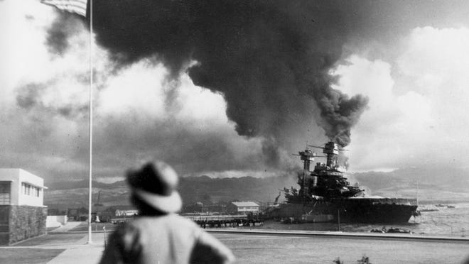 FILE - American ships burn during the Japanese attack on Pearl Harbor, Hawaii, in this Dec. 7, 1941 file photo. The coronavirus pandemic is preventing Pearl Harbor survivors from attending an annual ceremony to remember those killed in the 1941 attack. The National Park Service and Navy also are closing the ceremony to the public and livestreaming it instead.