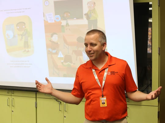 James Pollnow, a teacher with Oregon Connections Academy, reads during Jumpstart's Read for the Record Global Reading Challenge on Thursday, Oct. 22, 2015, in Salem, Ore.