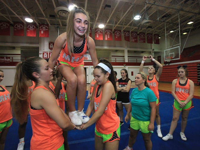 Kailey, cq, Campbell, 14, is lifted by Alex Revor, cq, 17, left, and Alaina Ratanapool, 14, right, as they learn a routine during practice for the Manual High School varsity cheerleading team. Aug. 20, 2014