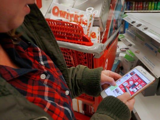 "A shopper checks out ""Black Friday"" deals on her smartphone at a Target on November 24, 2016 in Orem, Utah."