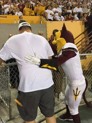 This photo courtesy of David Schapira shows a person dressed as ASU's mascot Sparky checking on David Schapira at a Arizona State University football game on Sept. 18, 2015 in Tempe, Ariz.  Schapira, a Tempe City Councilman, has filed a claim against Arizona State University for injuries suffered when the school mascot leapt on him on Wednesday, Nov. 11, 2015 The costumed character leapt on him at a football game two months after he underwent back surgery. The prank leap set back his recovery and led to a four-day hospital stay and physical therapy, Schapira said.