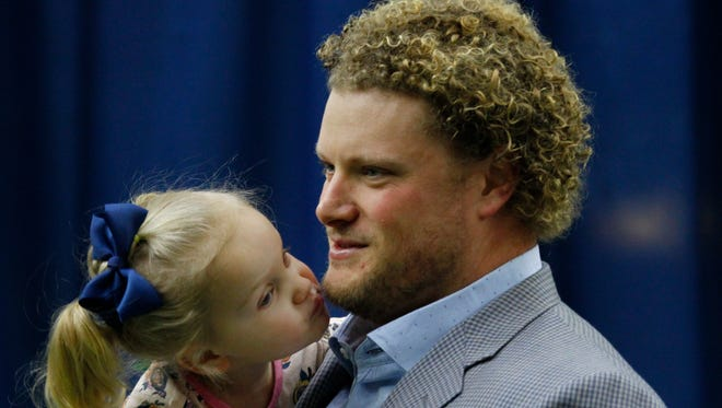 Buffalo Bills center Eric Wood is kissed by his daughter Grace following a news conference announcing he has been diagnosed with a career ending neck injury.