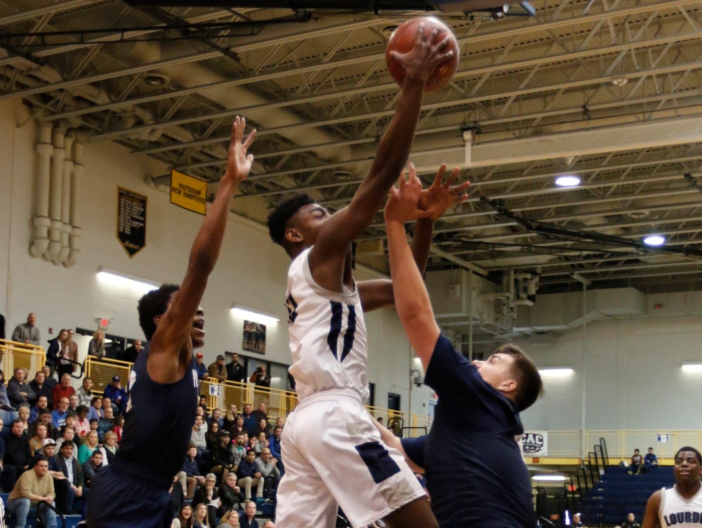 Our Lady of Lourdes High School's Kevin Townes splits two Poughkeepsie defenders during the Class A regional final at Pace University in Pleasantville on March 11.