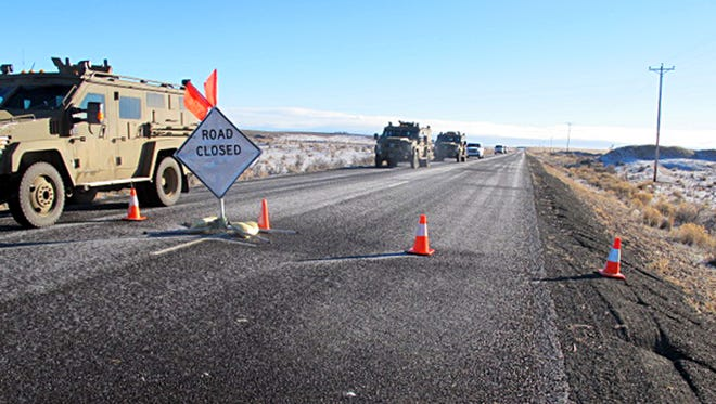 A convoy of armored vehicles and SUVs rolls past a barricade on the road near the Malheur National Wildlife Refuge near Burns, Ore., Saturday, Jan. 30, 2016. The remnants of an armed group occupying the refuge to protest federal land policies say they won't leave until they get assurances they won't be arrested.(AP Photo/Nicholas K. Geranios)